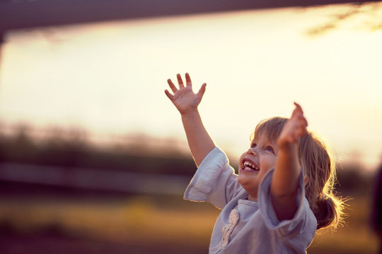 Happy kid looking at the sky . fun on countryside, sunset golden hour. Freedom nature concept.