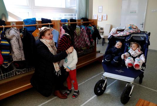 Lutheran pastor Boglarka Gyori, 31, dresses her 4-year-old son Lazar in the kindergarten in Kaposvar