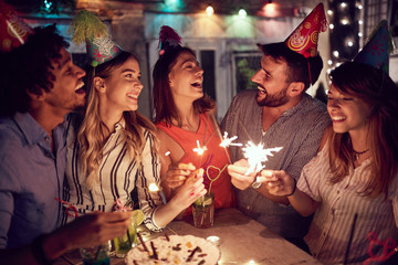 Smiling group of young friends having  birthday party in the club with cake and candles at night. ...