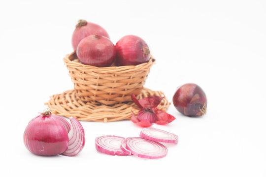 Raw purple onions, one cut, on white background. Organic, fresh purple onions in wicker basket. Healthy vegetable, Allium cepa.