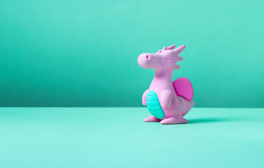 Cute rubber dragon toy on green background.