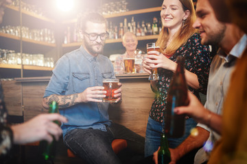 Group of friends drinking beer, chatting and having good time at pub. Night out.