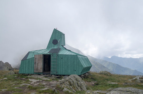 Green metal shelter on the shore of lake Caltun in the Carpathians, Romania