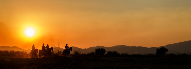 Silhouette cowboy group riding horseback in farm at sunset, landscape panorama, banner