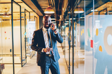 Happy confident black male manager talking on cellphone in corridor