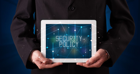 Young business person working on tablet and shows the digital sign: SECURITY POLICY
