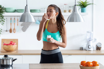 Sporty young woman eating iogurt while standing in the kitchen at home.