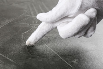 Person in white glove checking cleanliness of grey stone table, closeup