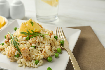 Delicious chicken risotto with lemon on table, closeup