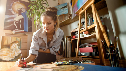 Beautiful caucasian white woman drawing the picture in interior. Working with paintbrush and paints. Warm atmosphere indoor. Nice soft light around