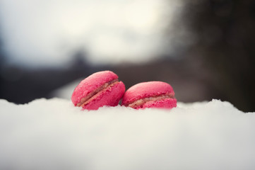 Homemade french pink macarons with raspberry cream on frozen snow background. Sweet delicious cookie