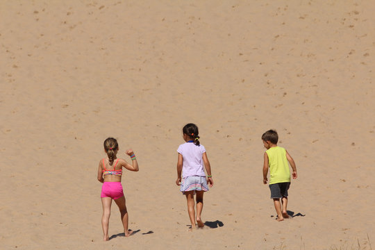 two young girls and and a boy walking up a sandhill