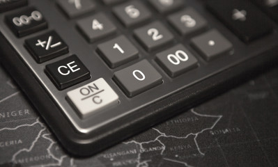 Close-up calculator on a map background, concept of billing information in business