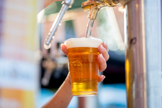 beer is poured into a glass from a tap. The bartender pours beer into a plastic glass