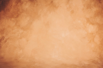 Vintage brown artistic canvas backdrop with vignette effect. Abstract stained background.