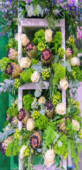 Beautiful vertical background of decorative flowers of roses and exotic proteas