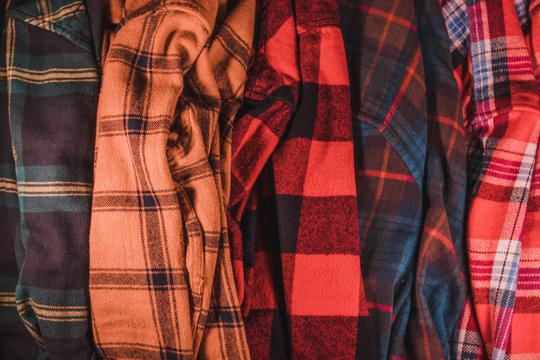 brightly colored checkered vintage flannel shirts lie together in a heap green yellow red blue orange