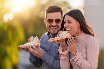 Picture of happy young couple eating pizza