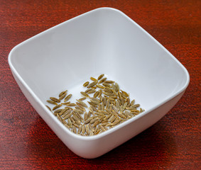 Macro shot of cumin seeds in a white bowl on a wooden table