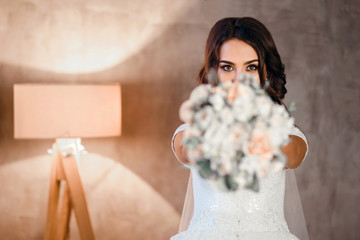 Bride having fun and hiding behind a bouquet of beautiful flowers, horizontal photo