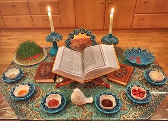 High Angle View Of Koran Amidst Foods And Lit Candles On Rug During Nowruz