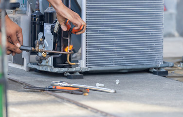 Close up of Air Conditioning Repair team use fuel gases and oxygen to weld or cut metals, Oxy-fuel welding and oxy-fuel cutting processes, repairman on the floor fixing air conditioning system Fotobehang