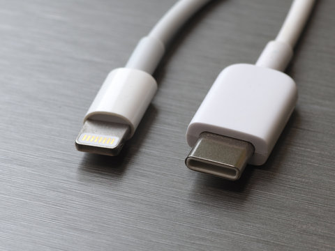 USB type C and lightning white cable connector on a gray metal background