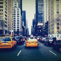 Fototapeta Rear View Of Vehicles On Road Along Buildings