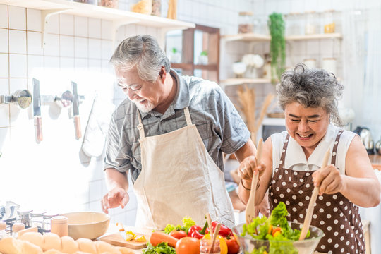 Couple senior Asian elder happy living in home kitchen. Grandfather cooking salad dish with grandmother with happiness and smile enjoy retirement life together. Older people relationship and lifestyle