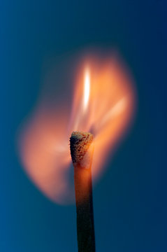 Close-Up Of Burning Matchstick Over Blue Background