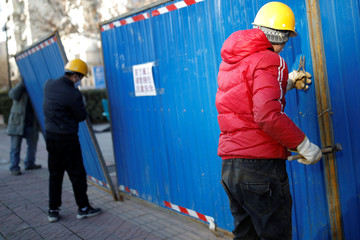 Workers assemble a temporary wall made of metal sheets outside a residential complexas the country is hit by an outbreak of the new coronavirus in Beijing