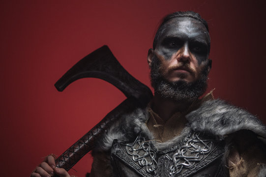 The Viking stands in a fighting position, pointing the battle axe towards the camera. A robber in armor and war paint looks madly at the camera holding an axe at the ready