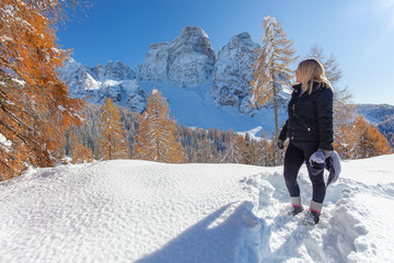 Blonde woman looking at a awesome Dolomite panorama and orange colored larch forest on a beautiful sunny day after a snowfall. Concept: fun in the snow, winter landscape, snow holidays
