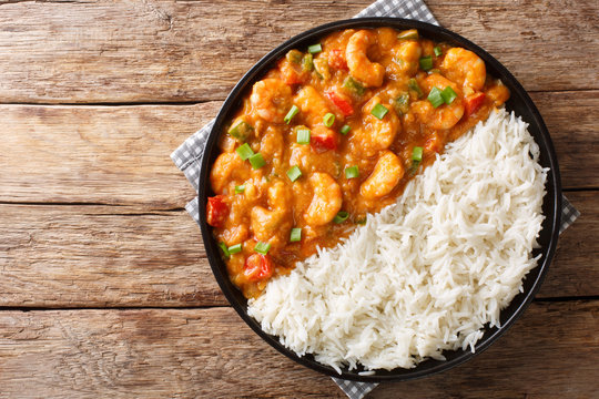 Serving of shrimp Etouffee with vegetables and sauce served with rice closeup in a plate. Horizontal top view