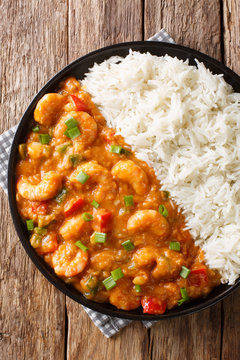 Shrimp Etouffee Juicy dish smothered in rich and flavorful roux sauce served with rice closeup in a plate. Vertical top view