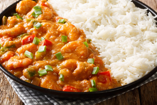 Louisiana shrimp Etouffee with vegetables cooked in roux sauce served with rice closeup in a plate. horizontal