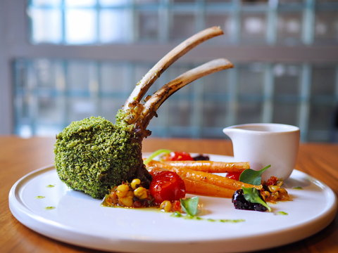 Perfectly grilled medium rare green herb crusted rack of Mottainai lamb from Australia gently prepared and served at a fine dining restaurant or cafe on white round plate on woonden table at Eureka