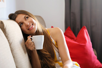 Young smiling woman sitting on sofa and looking up while drinking hot tea. Girl dreaming or thinking on couch at home in a leisure time.
