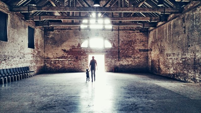 Rear View Of Father With Son Walking In Old Building