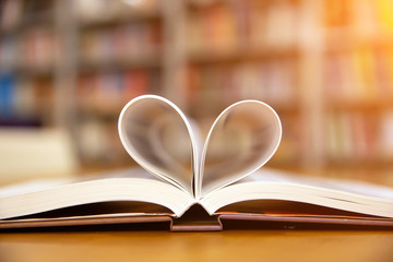 Close up book image in heart shape on the table at library room of lifestyle love to read and february valentine day concepts.