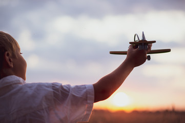 Happy child playing with a toy plane in nature during summer sunset. Boy in a  white shirt with a plane in hands on wheat field. Kid holds a wooden airplane and dreams of being a pilot, on the nature