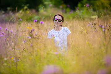 The girl in sunglasses on a flower meadow in the mountains