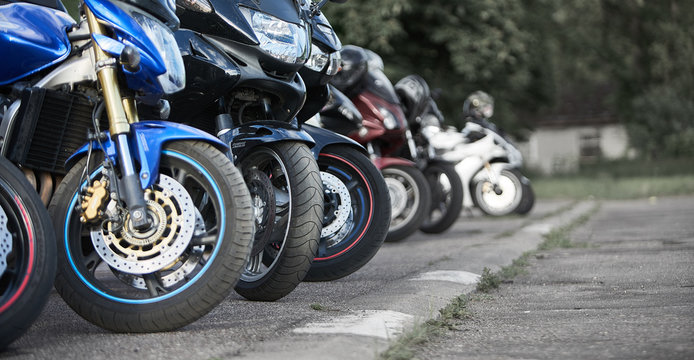 motorcycles standing in the row on asphalt closeup. Selective focus