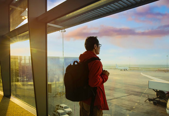 In the Airport with Back view of young  backpacker man  and a luggage which looking the airplane on the window  at a terminal airport