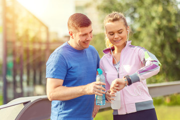 Happy sporty couple looking at heart rate monitor on smart watch after a run in park