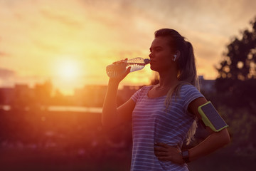 Modern sporty woman drinking water in park at dawn after intense jogging workout