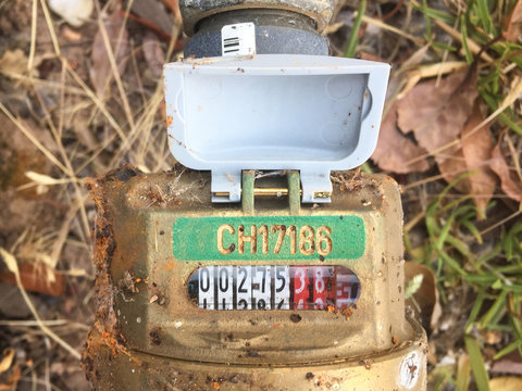 top-down view of a local council water meter with cover open to reveal measuring , , gauge