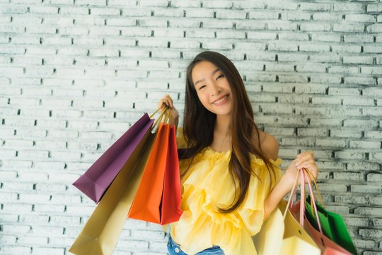 Portrait young asian woman holding colorful shopping bag