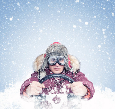 Driving man in red winter clothes and stylish goggles holds a steering wheel in his hands, around the snow. Front view
