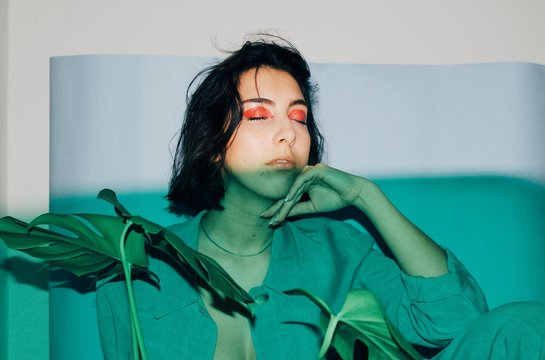 Portrait of a young woman with her eyes closed and monstera plant
